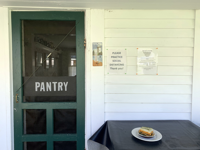 The Gosnold Pantry's contactless pickup station allows customers to safely pick up hot dinners, like Lucy Martin's vegan shepherd's pie. A sign on the wall asks customers to practice social distancing. (Alyce McFadden photo)