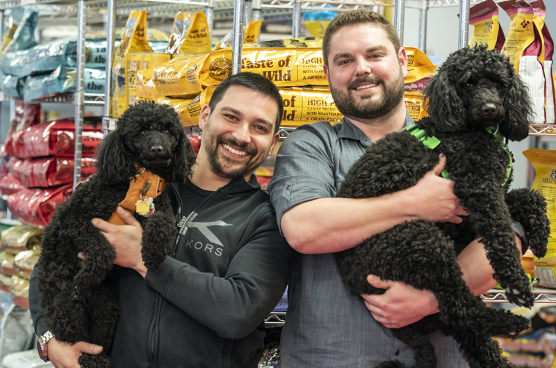 From left: Will Paul holds 4-year-old moyen poodle Zara while partner Branden Perreault holds Zara's 2-year-old sister, Kona, at The Animal House in Damariscotta on Saturday, April 25. Paul and Perreault bought the store at the beginning of April. (Bisi Cameron Yee photo)