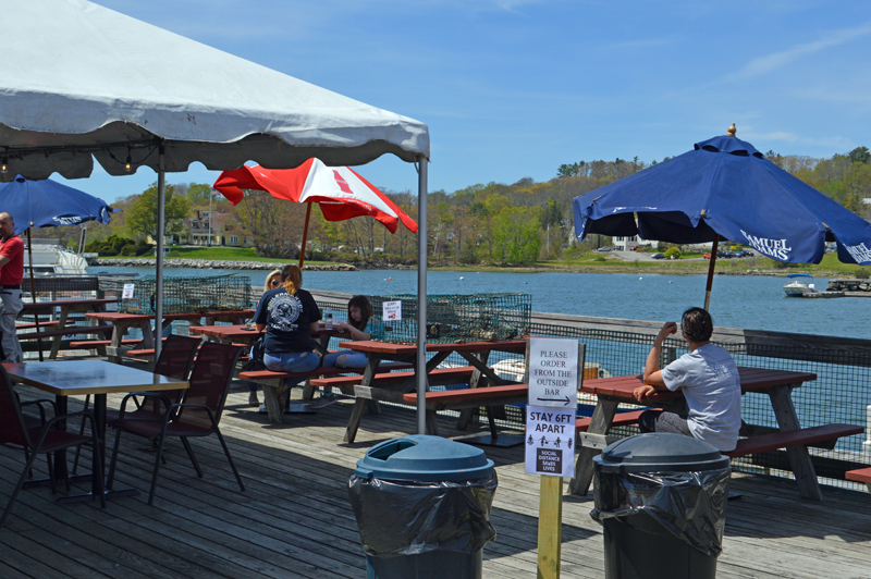 Lunch customers enjoy sun and seafood at Schooner Landing Restaurant and Marina in Damariscotta on Thursday, May 21. The restaurant is open for outdoor dining after a brief period with curbside pickup only. (Alyce McFadden photo)