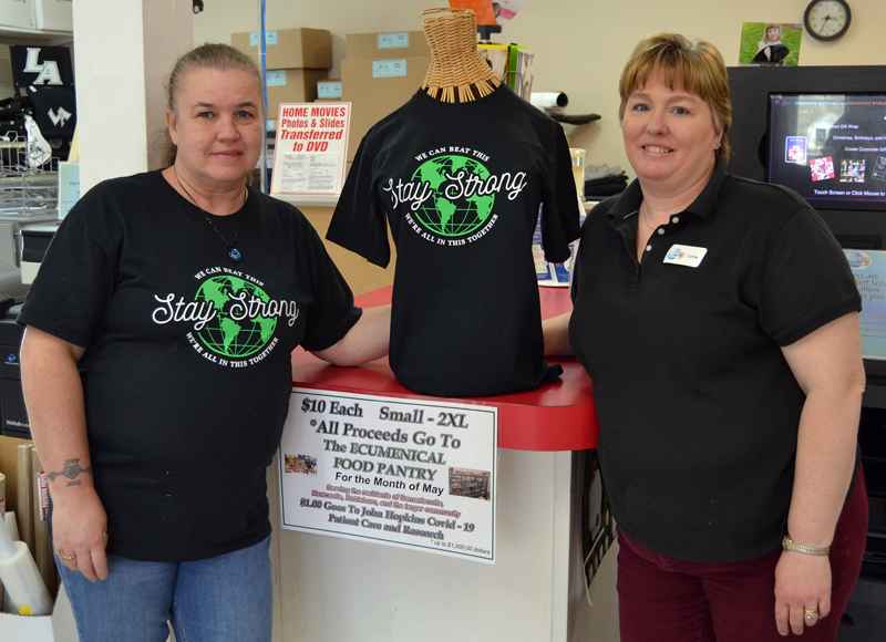 Mail It 4U co-owner Lynne Plourde (right) and customer service representative Sally Kenniston stand next to a mannequin wearing a Stay Strong T-shirt. The business is selling the T-shirts at its Newcastle and Bath locations, with 100% of the proceeds going to local food pantries.