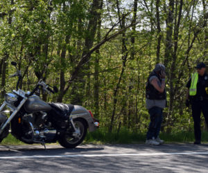 Douglas Humphrey (left) talks with Officer Cory Hubert at the scene of a motorcycle crash on Route 27 in Wiscasset, Wednesday, May 27. Police believe Humphrey's motorcycle and another motorcycle collided. (Evan Houk photo)