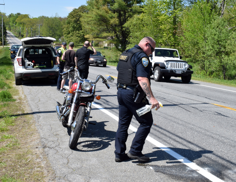 Wiscasset Police Chief Larry Hesseltine cleans up a crash scene on Gardiner Road in Wiscasset, Wednesday, May 27. An Auburn motorcyclist was flown to a Lewiston hospital with head injuries. (Evan Houk photo)