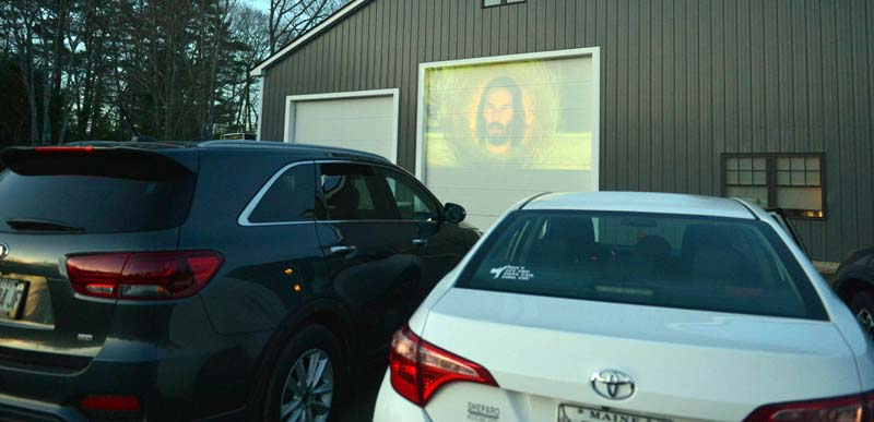 A preview of a movie plays on the garage door at Country Coach Charters in Nobleboro on Saturday night. (Paula Roberts photo)