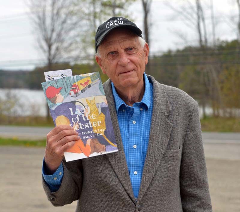 "The Rev. Frederick Lipp holds a copy of his newest children's book, ""Lady of the Lobster."" (Paula Roberts photo)"