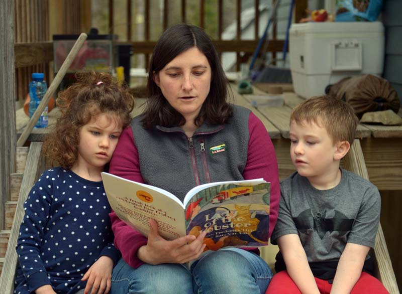 "Allison Roberts reads ""Lady of the Lobster,"" by local author Frederick Lipp, to her children, Michaela and James. (Paula Roberts photo)"
