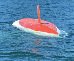 A capsized sailboat drifts in Back Cove, Waldoboro, Tuesday, May 19. The Waldoboro man on board climbed onto the bottom of the boat and held on until Friendship firefighters picked him up. (Photo courtesy U.S. Coast Guard)
