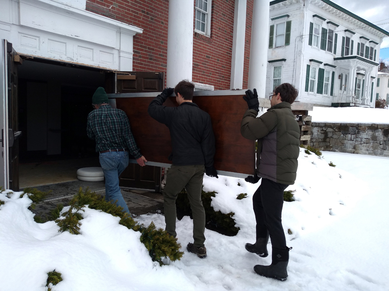 Davis and McMahon family members reinstall refurbished Waldo lobby doors.  (Photo courtesy Josie Davis)