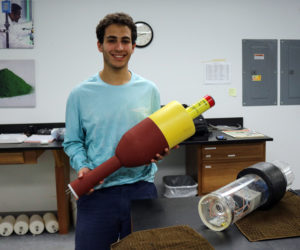 Joshua Girgis shows off a new low-cost environmental monitoring buoy he developed with a team at the Darling Marine Center in Walpole.