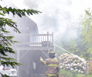 A Bristol firefighter directs the stream from a deck gun on top of a fire truck at a house fire at 159 McFarland Shore Road in New Harbor the moring of Wednesday, June 3. Bristol Fire Chief Paul Leeman Jr. said the house was a total loss. (Evan Houk photo)