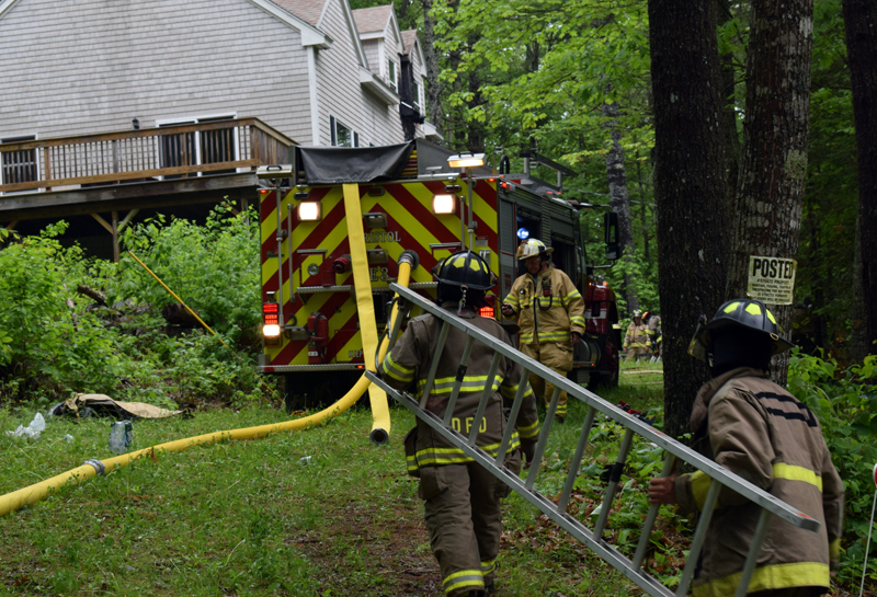 Firefighters carry a ladder to a house at 99 Atwood Lane in Bristol to assess the damage from a fire the afternoon of Saturday, June 6. A lightning strike caused the fire, which was quickly contained. (Evan Houk photo)