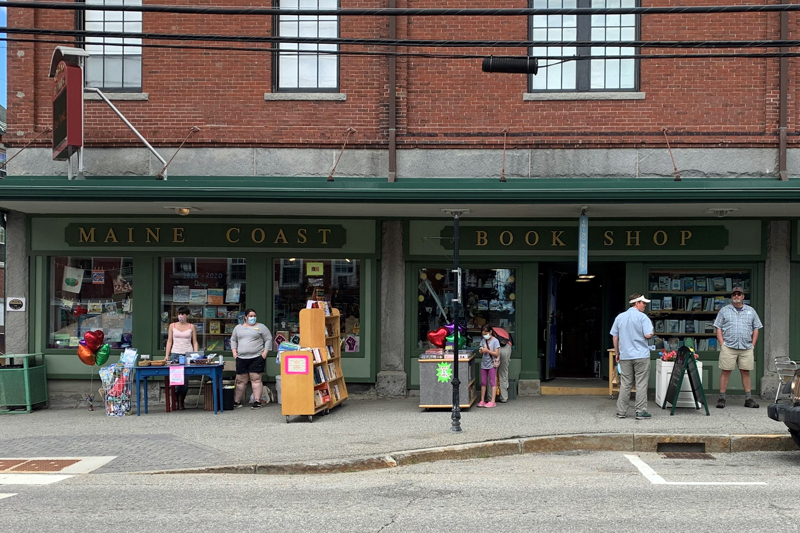 Customers browse bookshelves outside Sherman's Maine Coast Book Shop during the first open-air market in downtown Damariscotta, Saturday, June 13. The experiment aims to draw shoppers during the coronavirus pandemic. (Alyce McFadden photo)