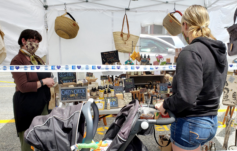 Du Jardin owner Susan Chalmers helps a customer from behind safety tape during the open-air market in downtown Damariscotta, Saturday, June 13. (Photo courtesy Jeff Friedman)