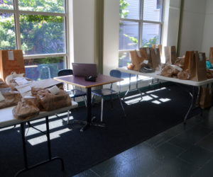 Bags of books await pickup in a hallway at Skidompha Library in Damariscotta. The library started offering curbside service Tuesday, June 16. (Alyce McFadden photo)