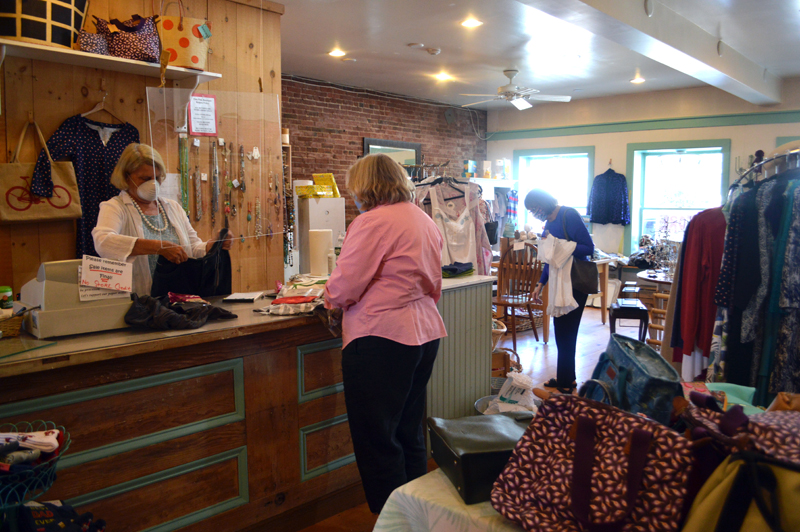 Two Fish owner Chris Hunt helps a customer during the boutique's closing sale. (Alyce McFadden photo)
