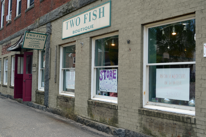 Signs in Two Fish boutique's front windows advertise the shop's closing sale. The shop closed for good Saturday, May 30, citing COVID-19. (Alyce McFadden photo)