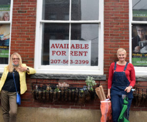 Finding Our Voices founder Patrisha McLean (left) stands with local volunteer coordinator Eve Jamison in front of 17 Elm St. in Damariscotta on Thursday, June 11. The duo hung nearly 50 banners in Damariscotta and Boothbay Harbor, including the one featuring McLean in the window at left. (Evan Houk photo)