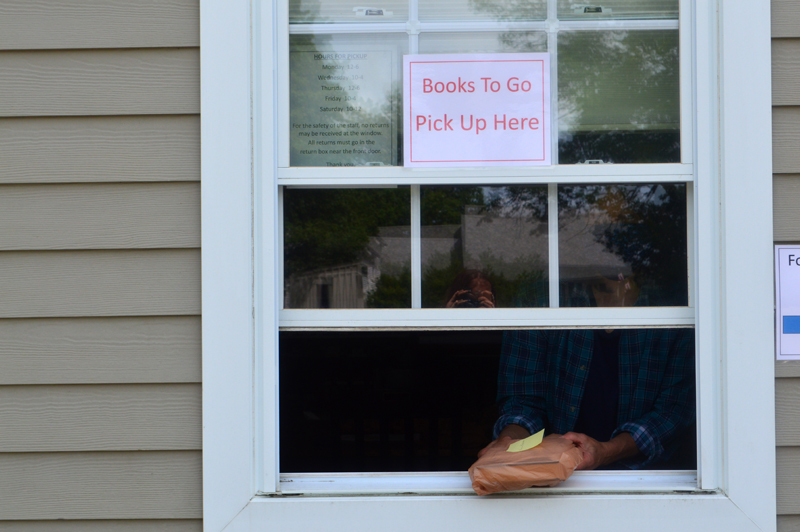 Cathrina Skov, director of the Waldoboro Public Library, passes a bag of books through her library's curbside pickup window. The library has been offering curbside service since May 12. (Alyce McFadden photo)
