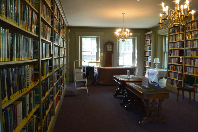 Furniture in the Wiscasset Public Library reading room is covered in plastic and pushed aside to discourage patrons from lingering. The library's full collection is open to the public for in-person browsing. (Alyce McFadden photo)