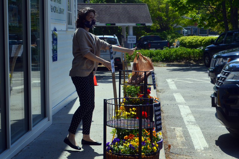 Desiree Scorcia, deputy director of community engagement and nonprofit management at the Boothbay Harbor Memorial Library, places a bundle of books in the library's parking lot for contactless pickup. (Alyce McFadden photo)