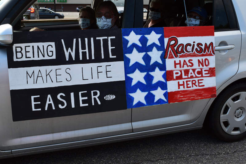 """Signs on the side of a car say """"Being white makes life easier"""" and """"Racism has no place here"""" during a mobile protest in Wiscasset on Friday, June 5. The Artists' Rapid Response Team made the signs. (Hailey Bryant photo)"""