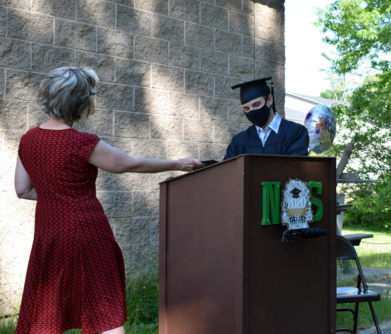AOS 93 Director of Curriculum, Assessment, and Instruction Ann Hassett presents Central Lincoln County Adult Education's sole 2020 graduate, Brandon Rodriguez, with his diploma during a ceremony outside Nobleboro Central School on Thursday, June 18. (Evan Houk photo)