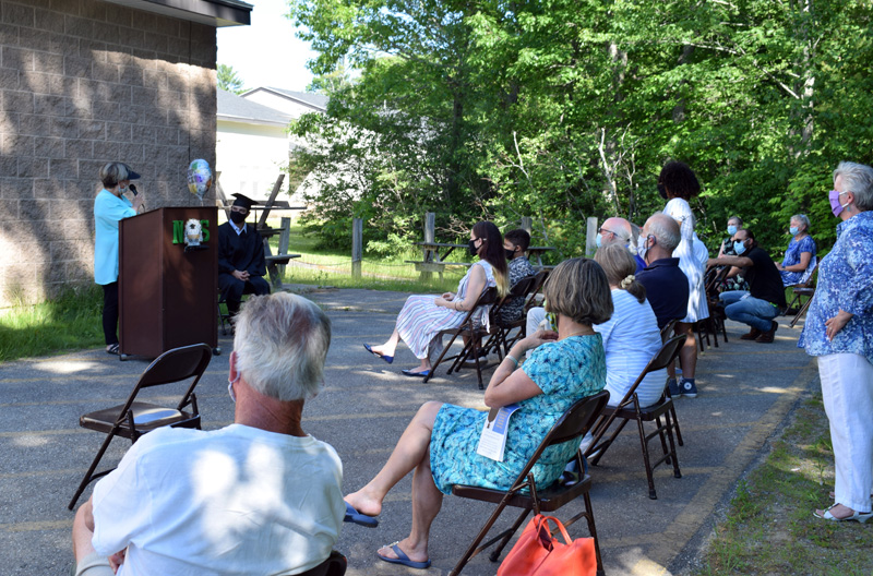 Central Lincoln County Adult Education Director Pamela Sperry addresses this year's lone graduate and a crowd of about 20 during a ceremony outside Nobleboro Central School on Thursday, June 18. (Evan Houk photo)