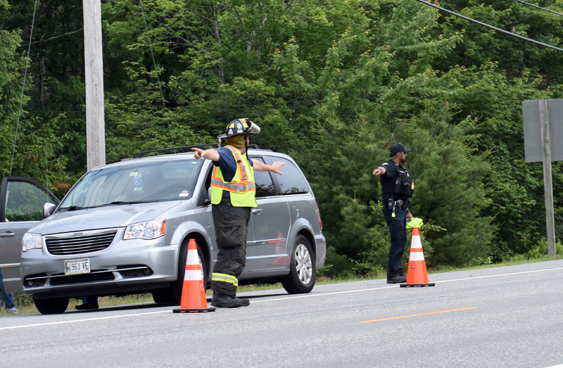 A Waldoboro firefighter and police officer direct traffic after a two-vehicle collision on Route 1, Tuesday, June 23. The minivan was one of the vehicles involved in the crash. (Alexander Violo photo)