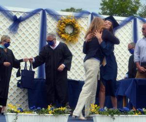 Medomak Valley High School Class of 2020 valedictorian Sadie Cohen embraces her mother during graduation Wednesday, June 10. (Alyce McFadden photo)