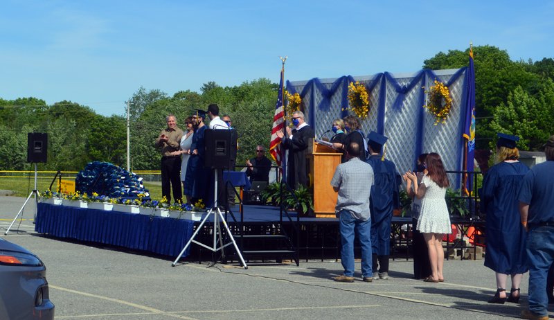Armando Louis Cabrero III receives his diploma as soon-to-be graduates and their families wait to the side during the drive-in graduation at Medomak Valley High School in Waldoboro on Wednesday, June 10. (Alyce McFadden photo)