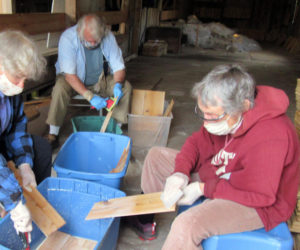 Volunteers Janice Haddock, Brad Craig, and Alexandra Jansen coat shingles with wood preservative at the Mill at Pemaquid Falls.