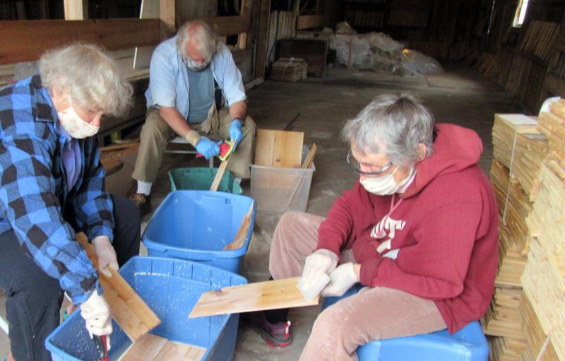 Volunteers Janice Haddock, Brad Craig, and Alexandra Jansen coat shingles with wood preservative at the Mill at Pemaquid Falls.