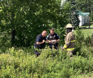 Damariscotta police and fire officers work at the scene of a motorcycle crash on Main Street in Damariscotta the afternoon of Wednesday, July 15. Both occupants of the motorcycle suffered severe injuries, police said. (Maia Zewert photo)