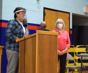 Robin Mayer, chair of the Damariscotta Board of Selectmen, dedicates the annual town report to longtime volunteer Ann Pinkham during the open portion of Damariscotta's annual town meeting on Wednesday, July 15. (Evan Houk photo)