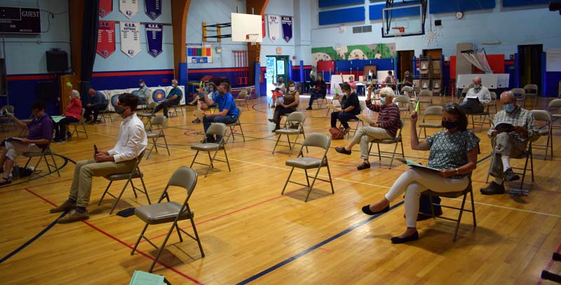 Damariscotta voters observe physical distancing and wear face masks during annual town meeting in the Great Salt Bay Community School gymnasium on Wednesday, July 15. (Evan Houk photo)
