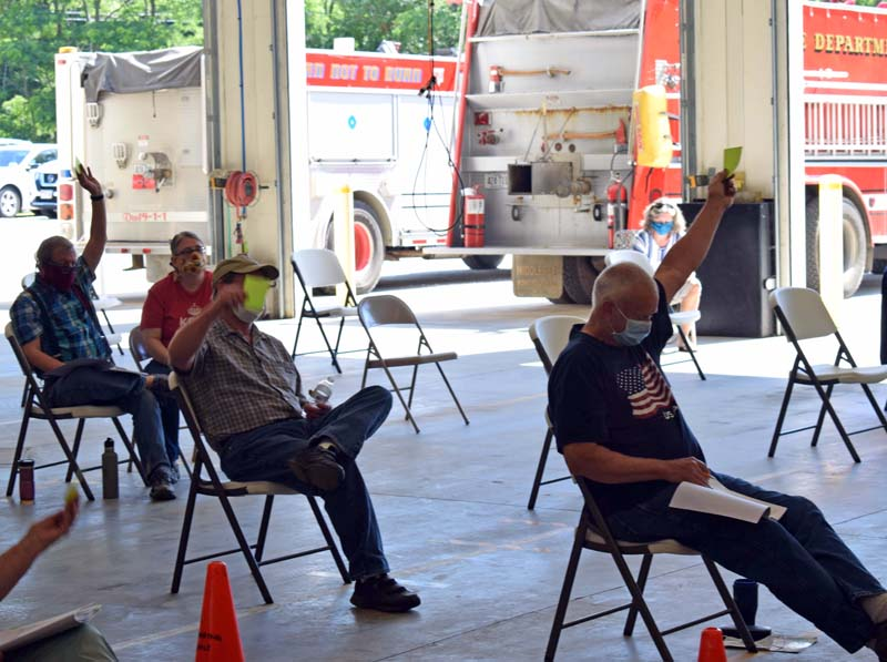 Dresden voters approve an article during annual town meeting at the fire station the morning of Saturday, July 18. The bay doors were open and chairs were set up with physical distancing in mind. (Evan Houk photo)