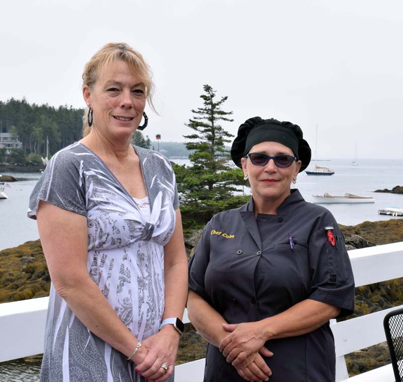 Lynette McGowan, the new owner of Coveside Restaurant and Marina, stands with the new head chef, Doris Rodriguez, on the front deck overlooking Christmas Cove, Friday, July 10. (Evan Houk photo)