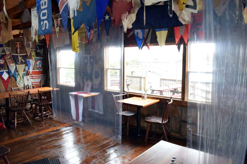 Plastic curtains provide separation between tables and different areas at Coveside Restaurant and Marina in South Bristol. (Evan Houk photo)