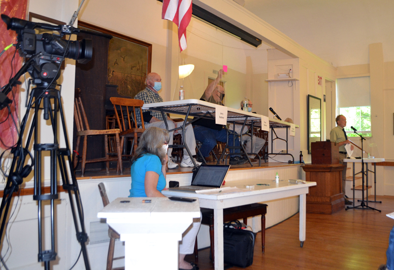 Westport Island Third Selectman Ross Norton raises his card in opposition to accepting a section of North End Road as a town way during annual town meeting at the historic town hall, Saturday, July 18. COVID-19 precautions at the meeting included face masks, Plexiglas barriers in front of the moderator and selectmen, and audiovisual equipment to connect voters at the town hall with those present in the community church next door. (Charlotte Boynton photo)