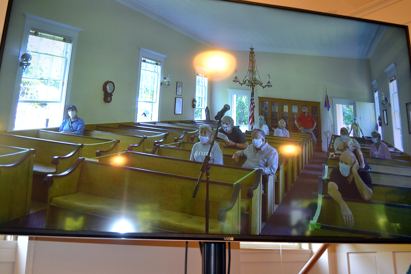 A screen at the historic town hall displays voters in the community church next door during Westport Island's annual town meeting Saturday, July 18. In a unique approach to physical distancing, audiovisual equipment connected voters in the church with those in the town hall. (Charlotte Boynton photo)