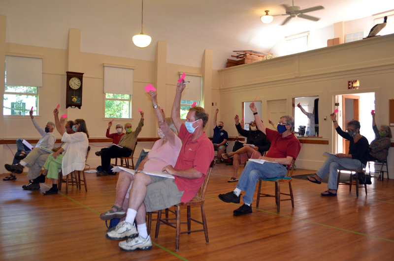Westport Island voters sit well apart and wear face masks as they raise their hands to accept a section of North End Road as a town way during annual town meeting, Saturday, July 18. (Charlotte Boynton photo)