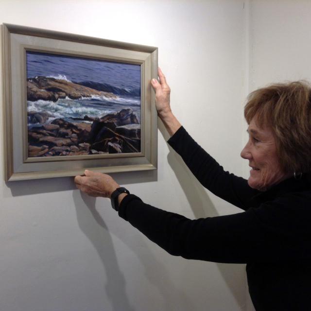Artist Caroline Howe hangs one of her oil paintings.