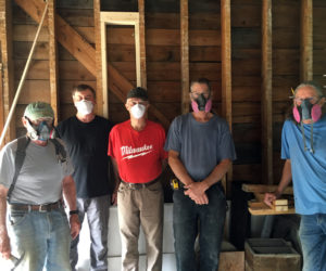 Volunteers and contractors wear masks for protection from dusty debris while renovating the building.