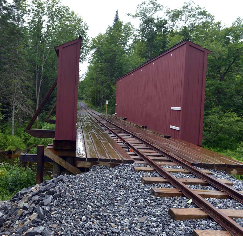 A Howe Pony Truss bridge over Trout Brook. Installed on the Wiscasset, Waterville & Farmington northbound line in 2019, it is one of three bridges remaining in North America that have this design. It is not a covered bridge in the true sense, as only the trusses are covered. (Paula Roberts photo)