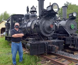 Wiscasset, Waterville & Farmington Railway Museum President David Buczkowski wears a WW&F face mask as he stands in front of Engines 4 and 8. (Paula Roberts photo)