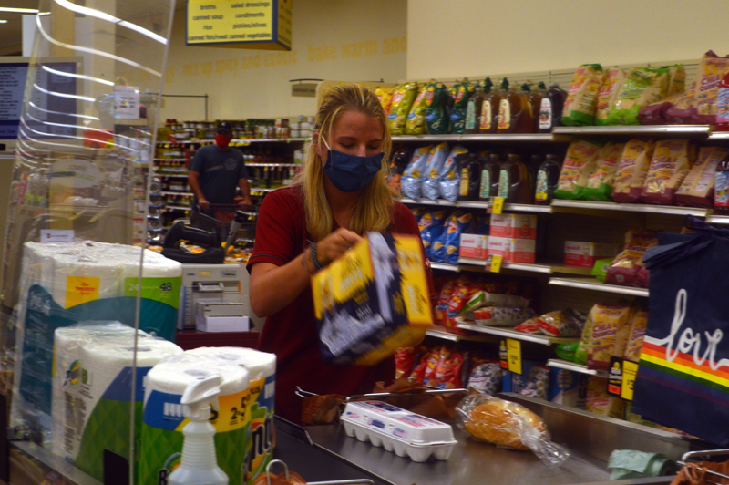 Sales Associate Irene Prescott checks out a customer at Hannaford Supermarket in Damariscotta. In April, Hannaford Bros. stores installed plexiglass barriers in checkout aisles and mandated mask-wearing for employees, among other safety precautions. (Alyce McFadden photo)
