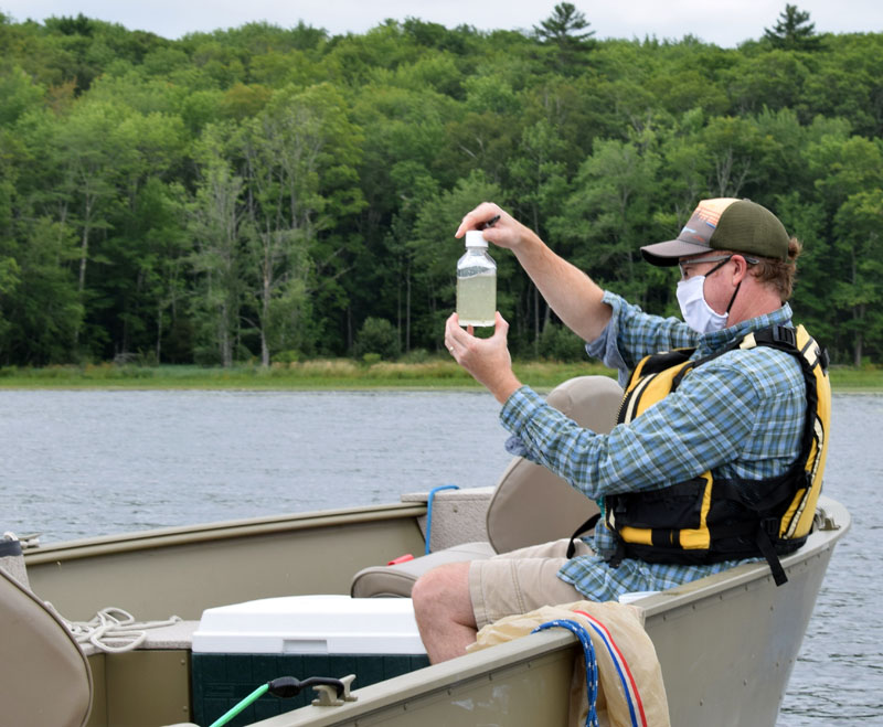 Peter Countway, a senior research scientist at Bigelow Laboratory for Ocean Sciences in East Boothbay, examines a water sample on Damariscotta Lake, Saturday, Aug. 15. (Evan Houk photo)