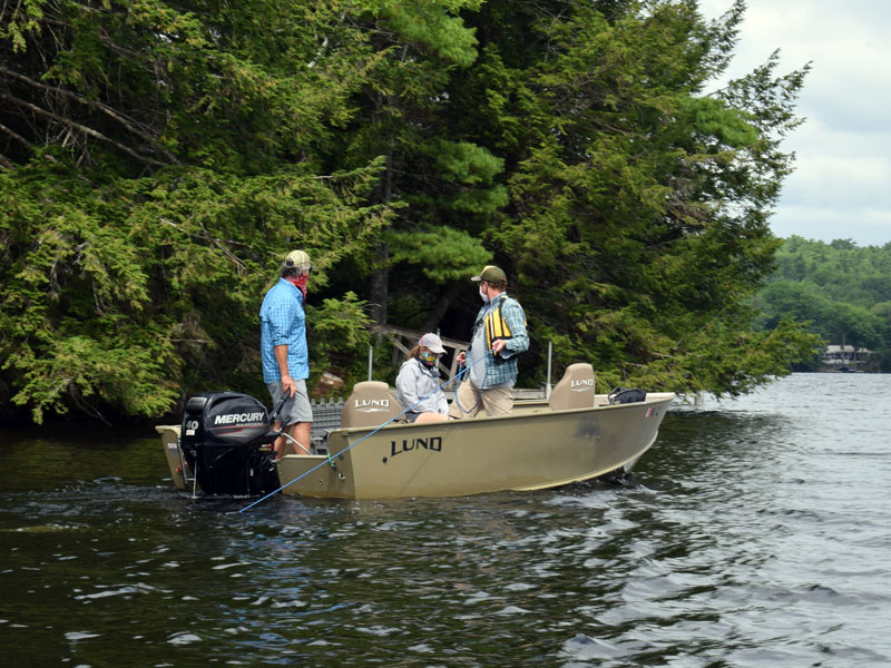 Peter Countway, a senior research scientist at Bigelow Laboratory for Ocean Sciences in East Boothbay, takes water samples near Hatch Cove in Damariscotta Lake on Saturday, Aug. 15, as lake resident Sandy Buck (left) and Patricia Nease, Railsback Maine Conservation Corps water steward, look on. (Evan Houk photo)