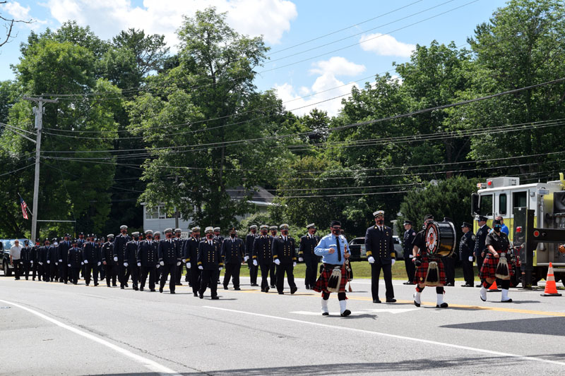 The Bergen County Firefighters Pipe Band and the Hackensack Fire Department, both of New Jersey, march on Route 1 in Wiscasset to honor Hackensack firefighter Richard Kubler. Kubler, 53, of Wiscasset, died July 25 of cancer linked to his service at ground zero after the 9/11 terrorist attacks. (Hailey Bryant photo)