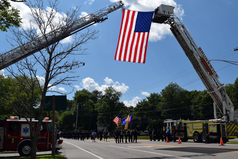 Fire trucks from Bath and Brunswick hold an American flag over Route 1 in Wiscasset, Saturday, Aug. 1, during a procession in honor of firefighter Richard Kubler. (Hailey Bryant photo)