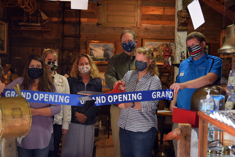 The owners of Skipjack Marine Gallery and representatives of the Damariscotta Region Chamber of Commerce cut the ribbon for the new business in Round Pond on Friday, Sept. 11. From left: chamber representatives Kristy Battles, Jeniffer Cooley, and Lisa Hagen; owners Joe and Alison Elder; and chamber President John Roberts. (Hailey Bryant photo)